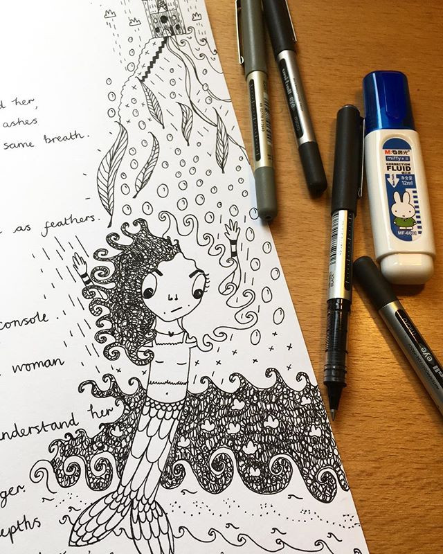 Pens next to a piece of paper with a mermaid drawn in black ink next to a poem (unreadable)