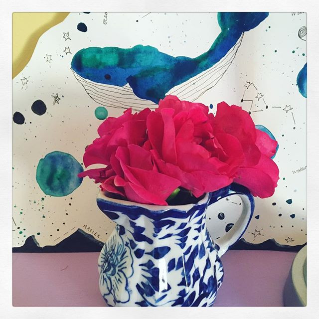 Photo shows some pink roses in a small blue and white jug with a painting of a whale floating in space in the background