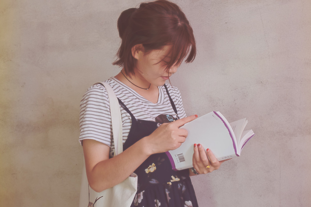 photo of a woman of East Asian heritage reading a book