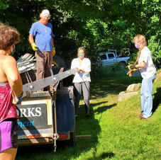 Volunteers unloading greenhouse frame to be stored in local barn