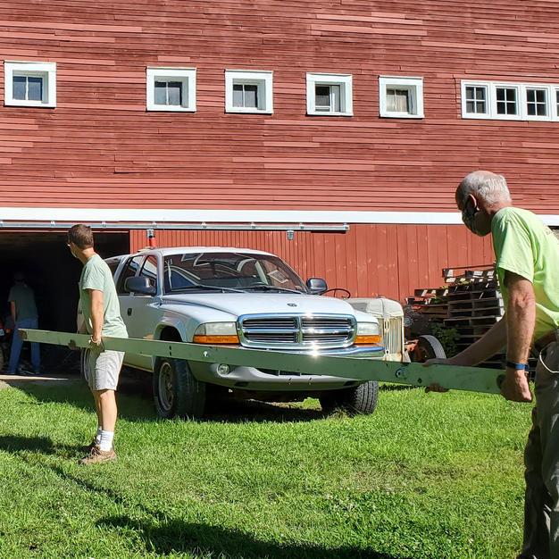Volunteers moving steel frame into storage