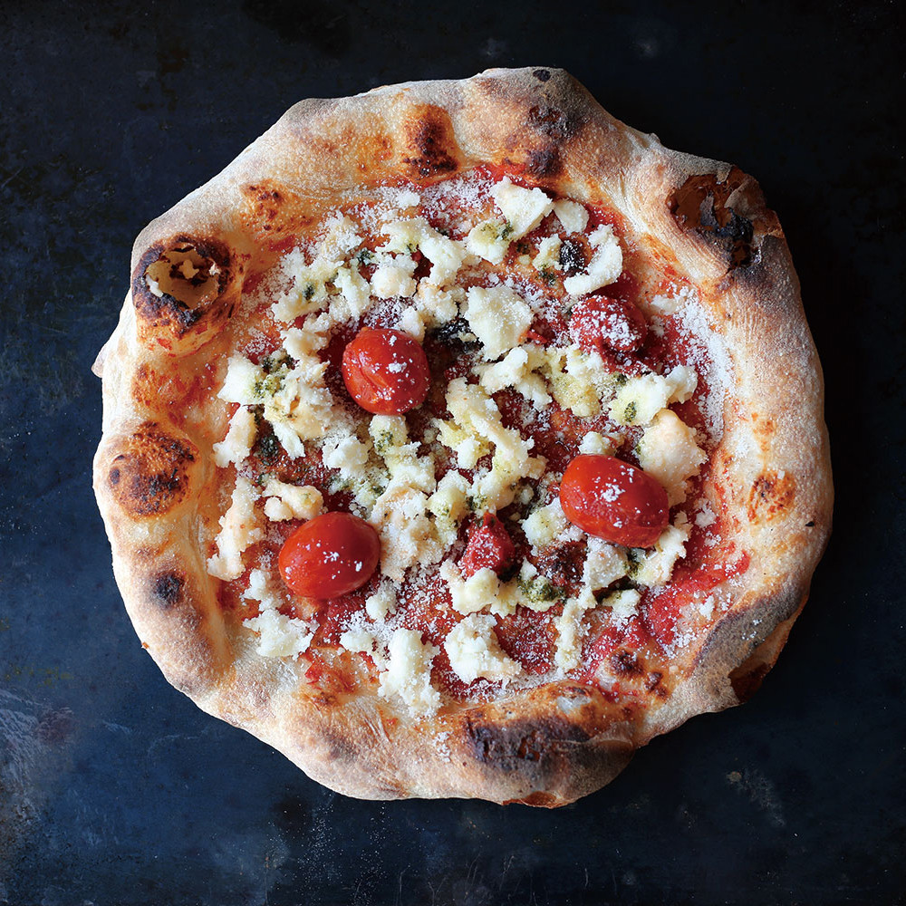【 Pizza Tamaki 】 PSTの看板メニュー。スモーキーな香りが特徴のスモークモッツァレラチーズとチェリートマトとの絶妙なマリアージュ。チェリートマトを潰しながら食べることでジューシーさを味わいながらもスモーキーな香りも楽しめるイチオシのいちまい。