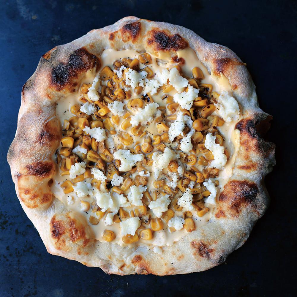 【 Pizza からしマヨ焦がし醤油コーン 】 店舗では提供していない、冷凍ピザでのみ食べられるテイスト。このマヨコーンピザ、マヨはからしのきいたツンとする自家製からしマヨソース、コーンは醤油で焦げ目をつけた焦がし醤油コーン。いちど食べたら病みつきになるマヨコーン好きにはたまらない大人テイストのいちまい。
