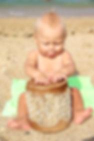 a baby boy plays a shamanic drum