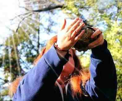 a shaman student practices smudging in bright sunlight