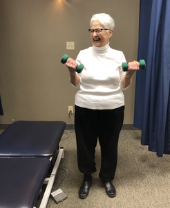 older patient performing resisted strength training exercises at physiotherapy clinic