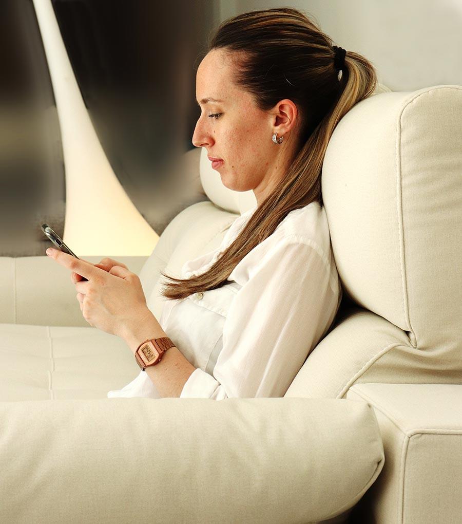 Chica con posición correcta sentada en un sofá, que además lleva un armazón de Mapay. El cuerpo está relajado.