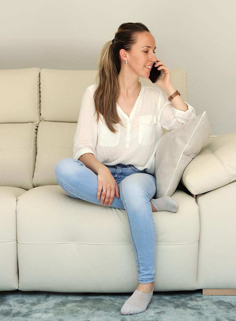 Mujer sentada sobre la pierna en un sofá.