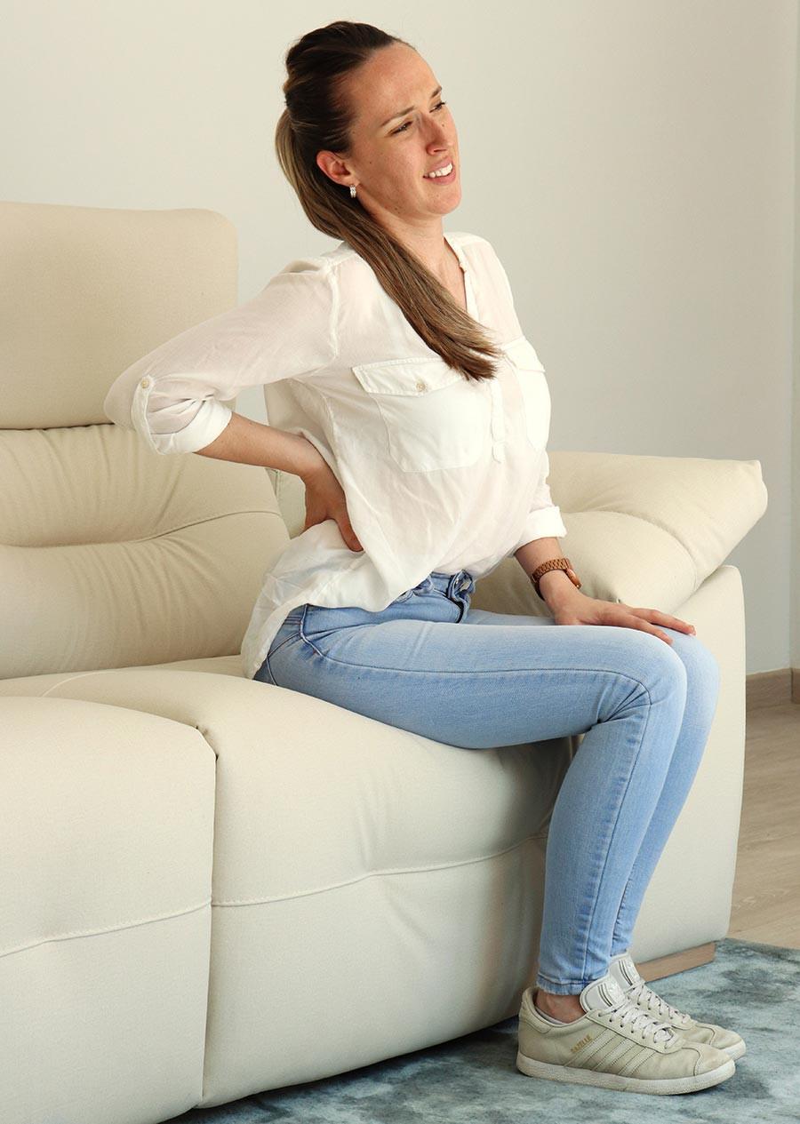 Persona con dolor en la zona lumbar tras una mala postura en el sofá, que puede dañar la espalda