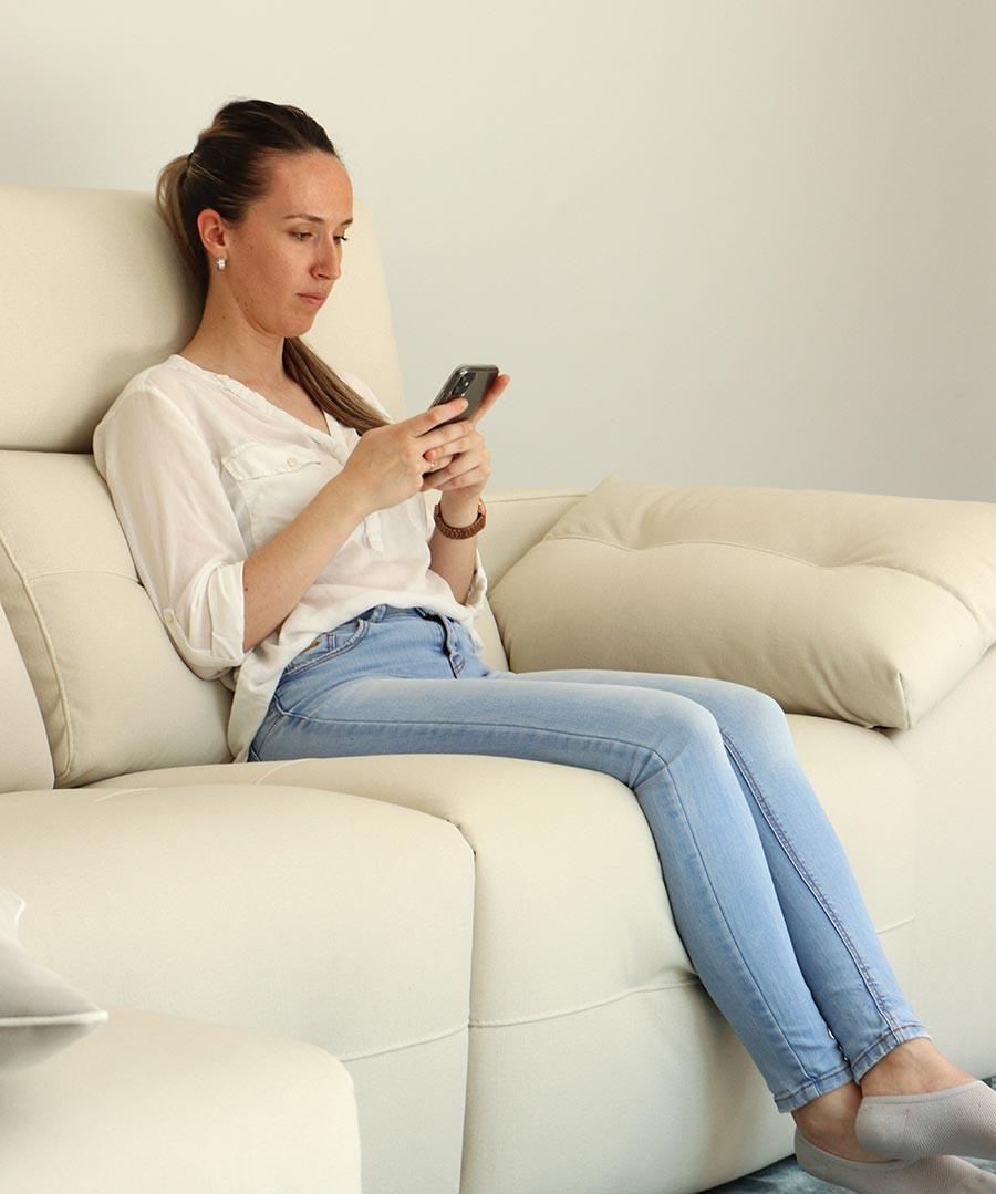 Chica sentada en sofá con la columna bien alineada