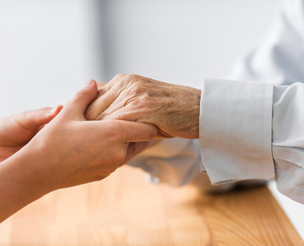 nurse-holding-senior-man-s-hands-comfort