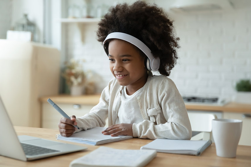 Smiling small African American girl in headphones watch video lesson on computer in kitche