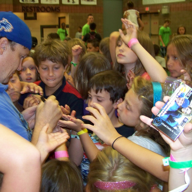 Michael Darby signing autographs for kids after a performance at the YMCA.