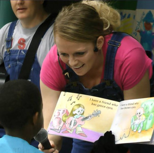 """Smalley Elementary student reading a page out of book """"I Have a Friend Who..."""""""