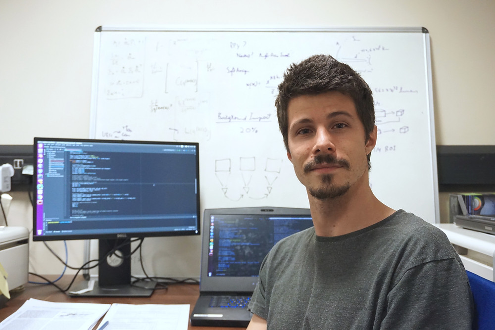 Pedro sitting in front of his desk, facing the camera and slightly smiling. Behind him is a laptop and screen showing programming code and a white board with drawings and equations.