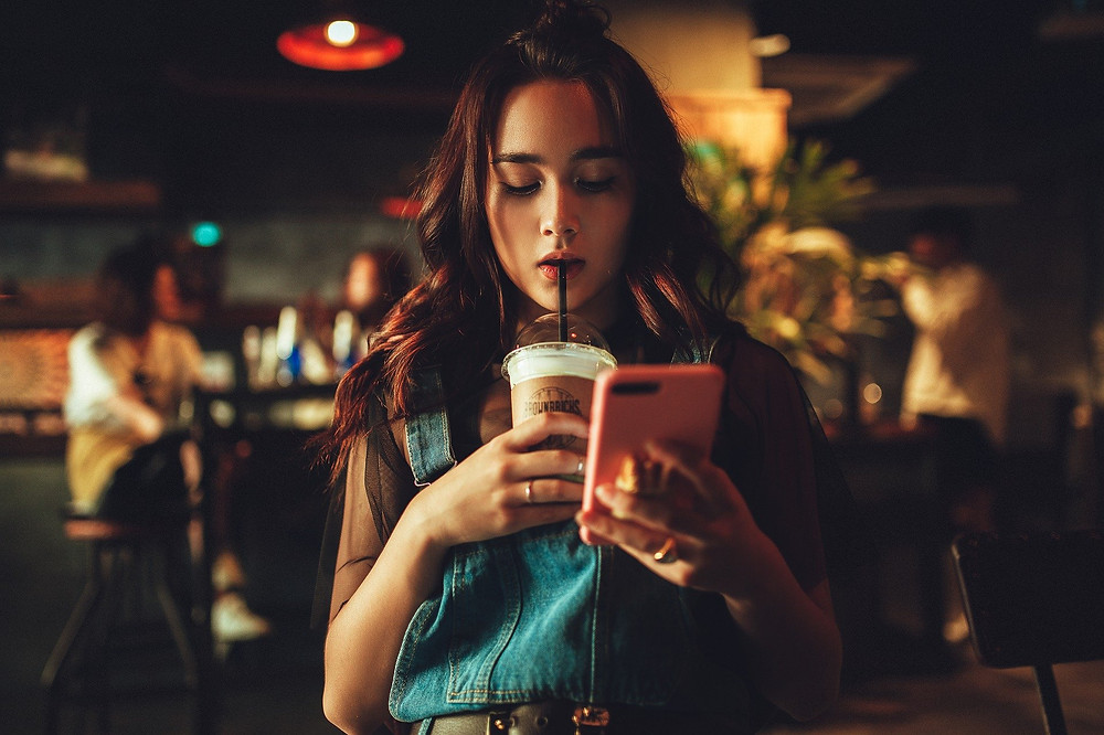 Woman looking at her phone - how to reduce your screen time