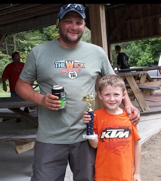 Keegan Burke holding the 2nd place trophy with his dad Joe, for best restored 72 Ski Doo TNT