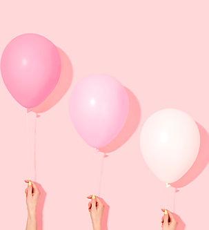 Manos sosteniendo globos