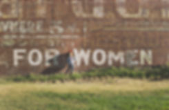 """Girl leaning against brick wall that says """"For Women"""""""