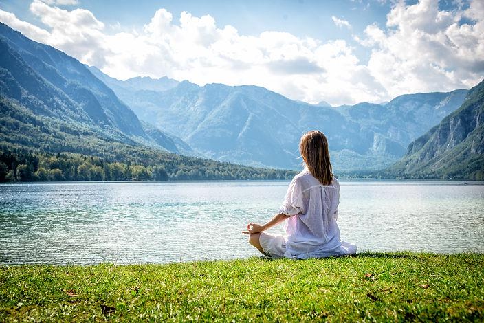 Woman Meditating by a Mountain Lake