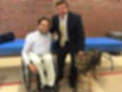 Picture of a man with a guide dog and a man in a wheelchair