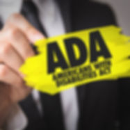 Man holding a yellow sign that says ADA Americans with Disabilities Act