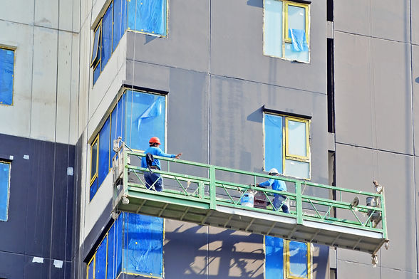 Two workers were painting wall of buildi