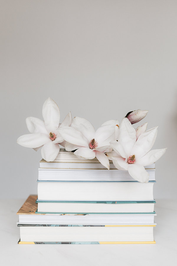 stack-of-books-with-magnolia-flower-on-w