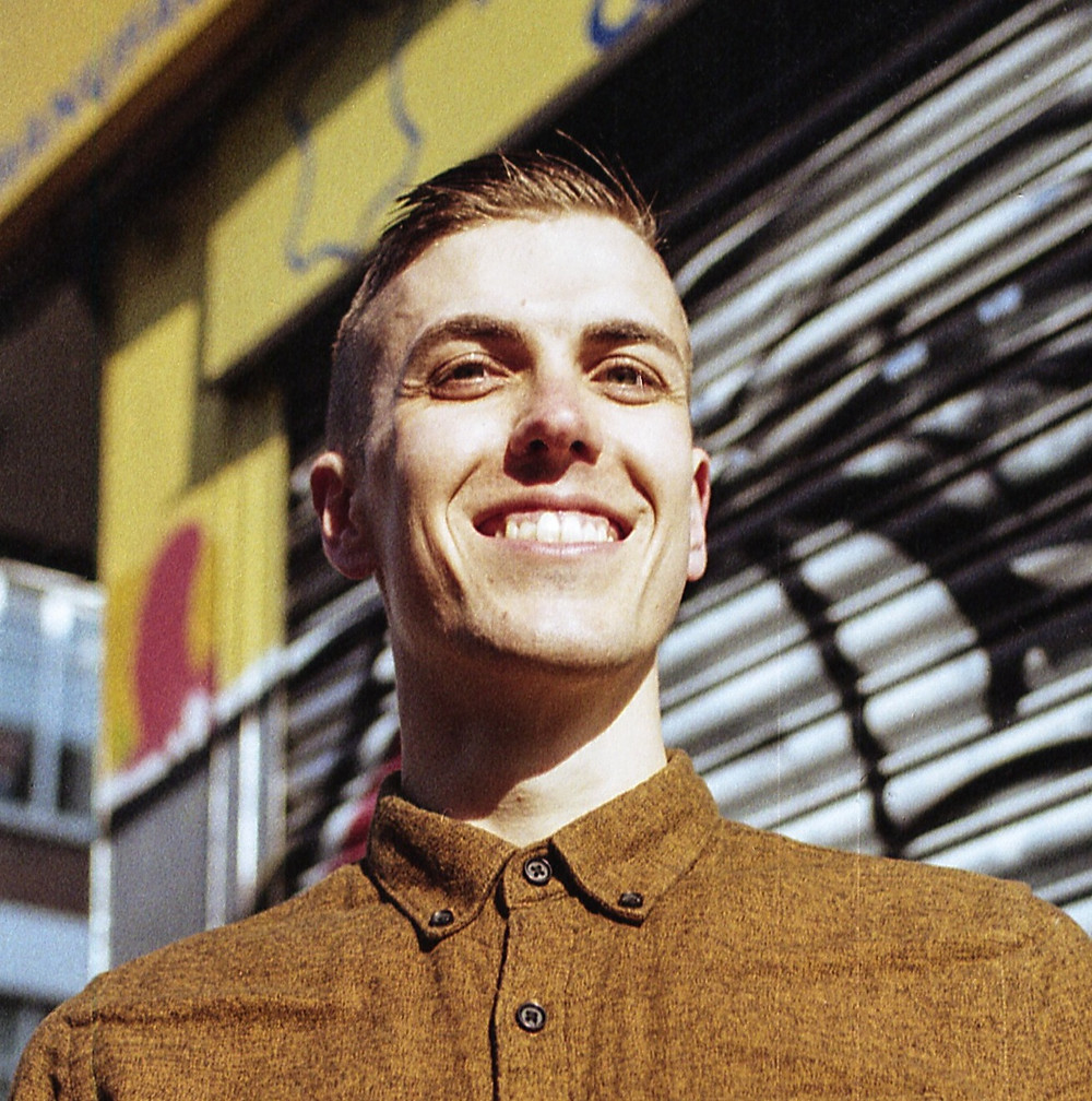 Alex looks down at the camera smiling, with a brown, flannel button-down shirt and short brown hair styled in a comb over. Alex stands in front of a yellow shopfront with graffiti on the shutters.