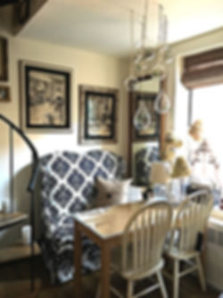 Black and white interior and exterior illustrations framed above an Ikat Pattern Settee with warm white Windsor Chairs create dining space in small NYC apartment