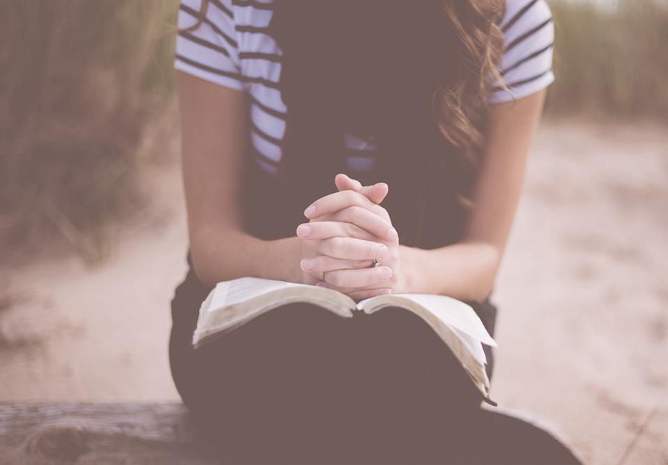 Una mujer se sienta con una Biblia abierta y reza.