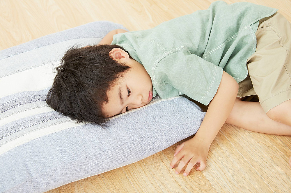 young boy lying listlessly on the floor