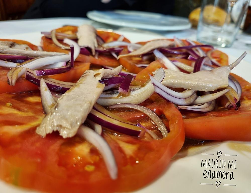 Ensalada de tomate rosa con ventresca y cebolla morada.