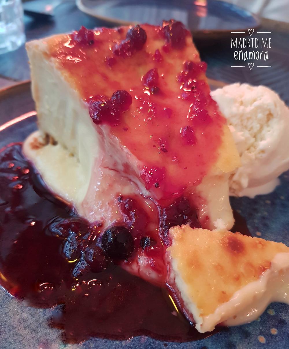 Tarta cremosa de queso con salsa de frambuesa y helado.