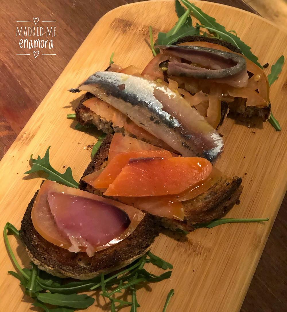Semisalazones de bonito, sardina, caballa y salmón presentados en una tosta con tomate rallado.
