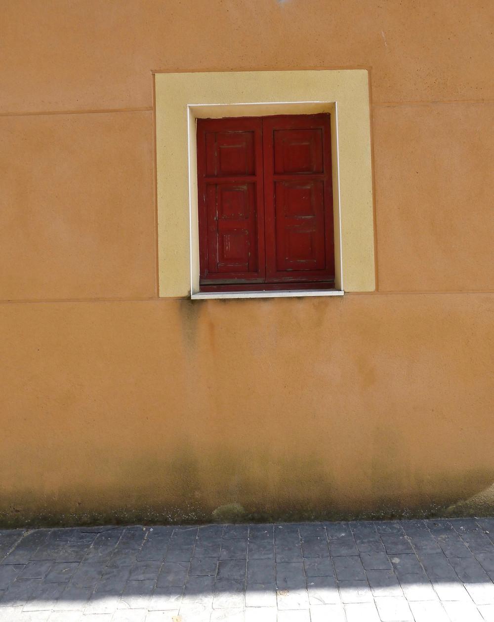 Red wooden shuttered window in Spain
