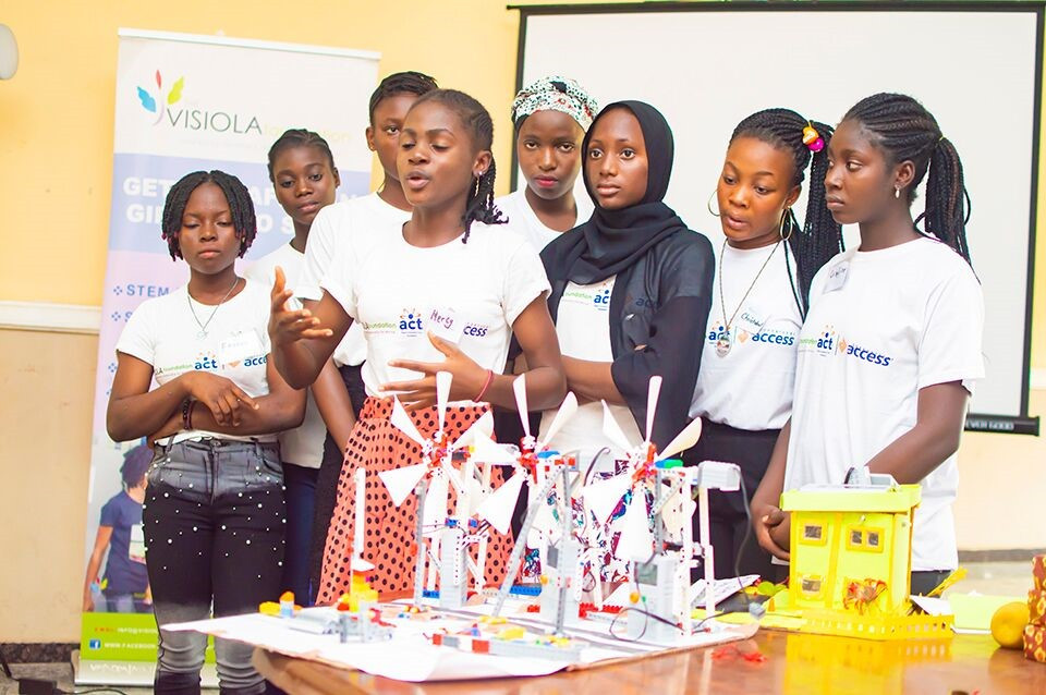 A group of girls standing at the front of a classroom, explaining a project