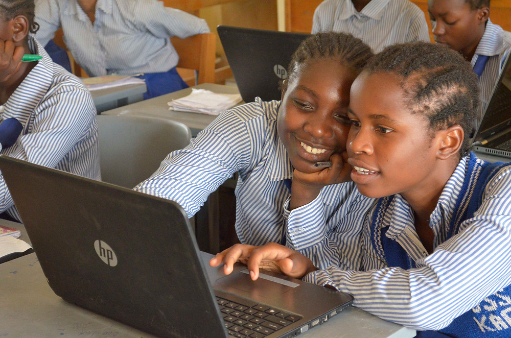 Two smiling girls working on a laptop computer