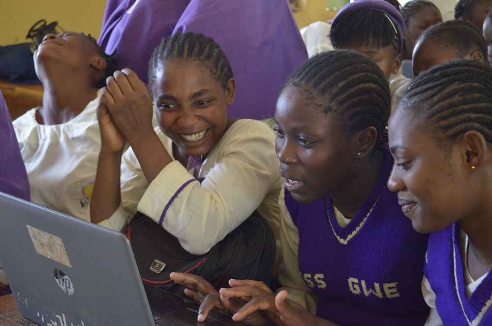 Smiling girls working on a laptop computer together