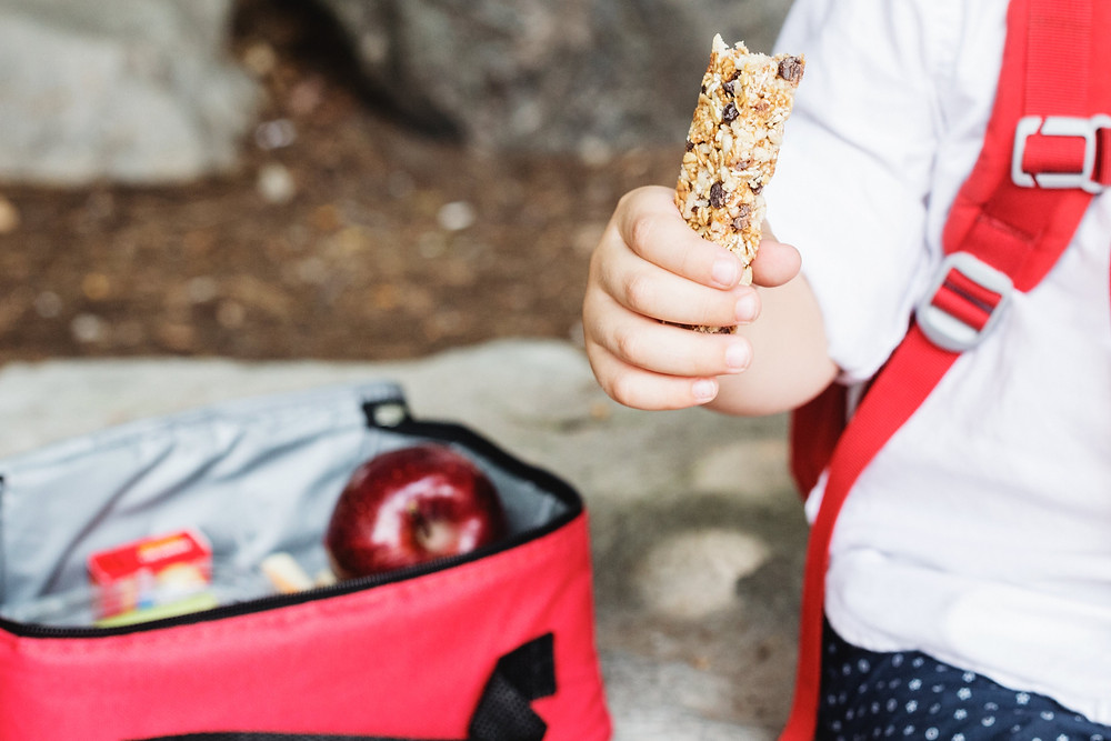Child eating healthy snacks from a lunchbox