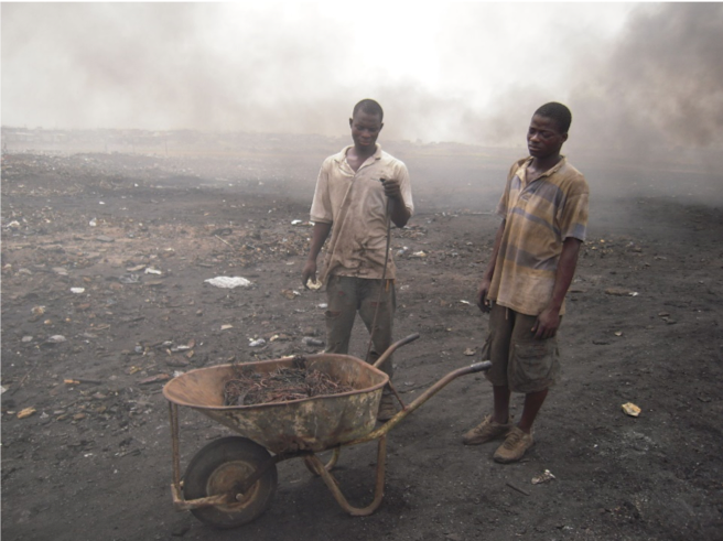 E-waste workers in Agbogbloshie, Ghana, completing a burn for copper recovery