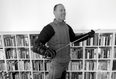 Damon Young in his home library with broadsword, Hobart, Australia.