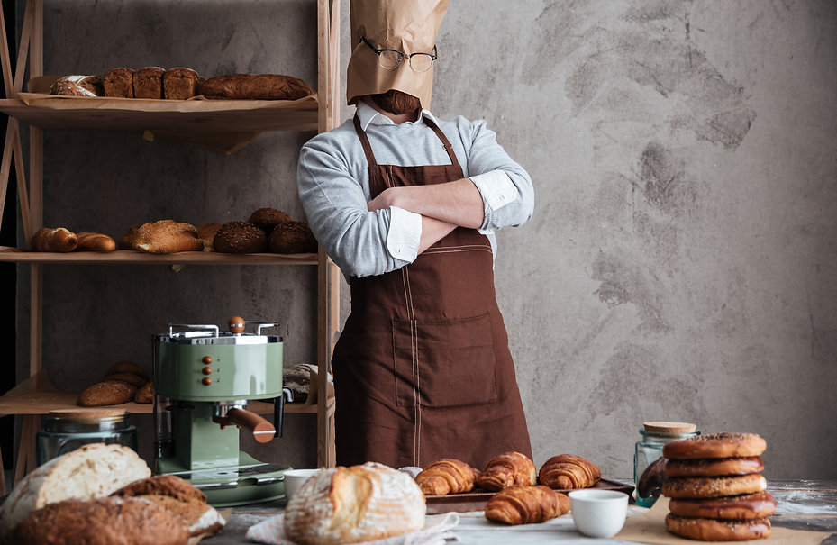 an-baker-standing-at-bakery-near-bread-P