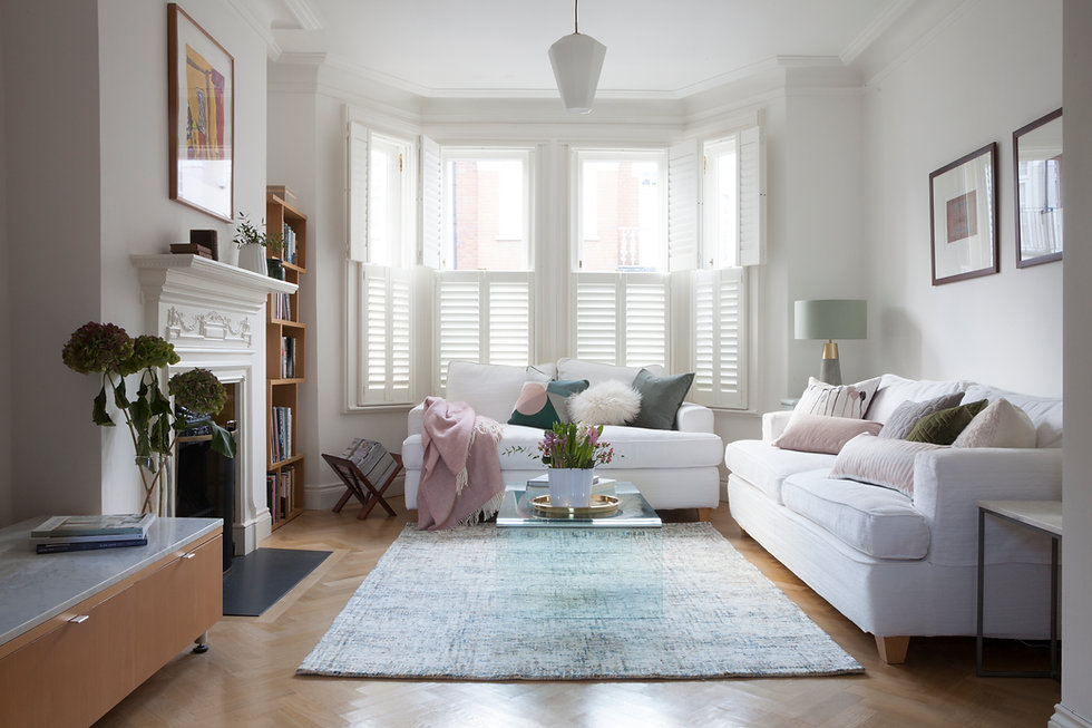 Beautiful living room with white walls, sofas, shutters and pastel cushions and rug