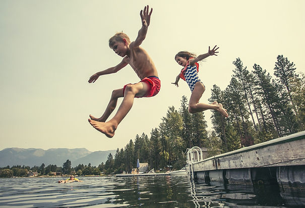 Kids jumping off the dock into a beautif