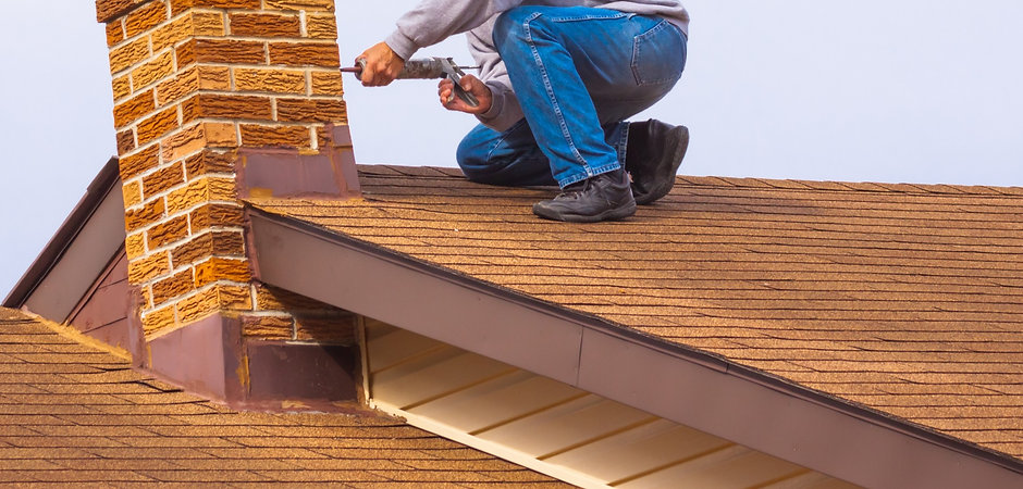 Contractor Builder with blue hardhat on the roof caulking chimney_edited.jpg