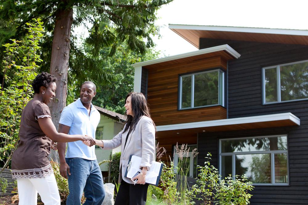 Consultor imobiliário fechando negócio com seus clientes felizes.