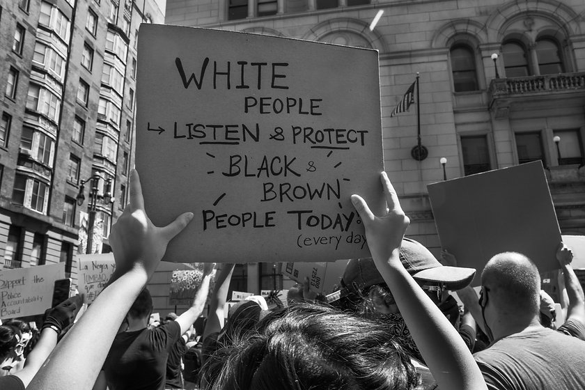 "A sign is raised in the air that says ""White people, listen and protect black and brown people today and every day"""