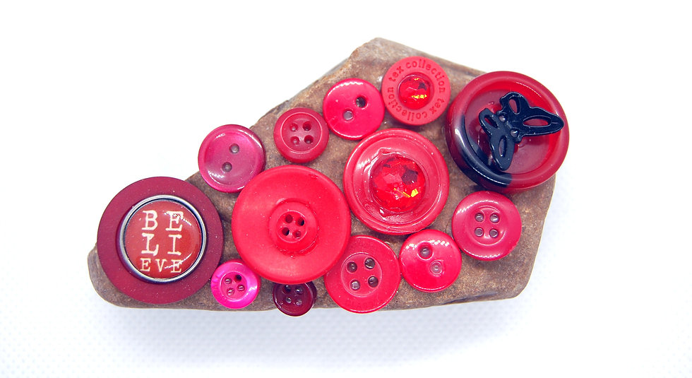 Stone paperweight covered in red buttons