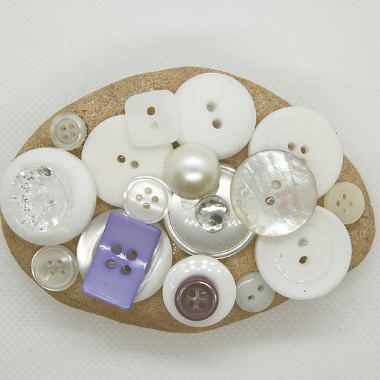 Stone paperweight covered in white buttons